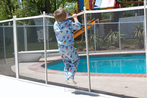 image of child attempting to climb over removable pool fence